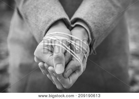 Woman's hands tied with rope black and white