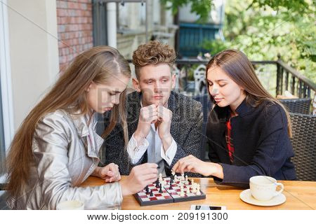 Two teen girls and a hipster guy relaxing and playing chess at the cafe on a blurred background. Friends competing in a chess game outdoors.