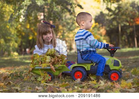 Little Boy And Girl Playing In The Park On A Beautiful Autumn Day