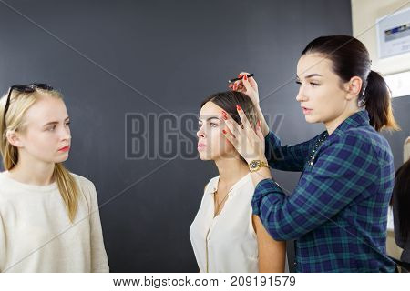 The make-up artist is applying makeup to the young girl. In the studio on a black background.