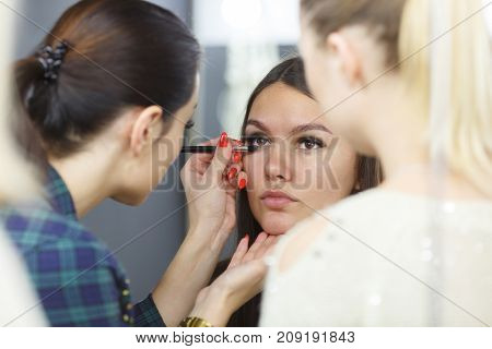 The make-up artist is applying makeup to the young girl. In a studio. Close-up.