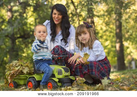 Mother Plays With Her Children In The Park In Autumn