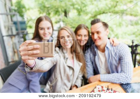 Friends who have fun in a cafe. Do selfie. Blurred background. Concept of leisure.