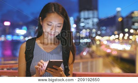 Woman use of cellphone in Hong Kong in the evening