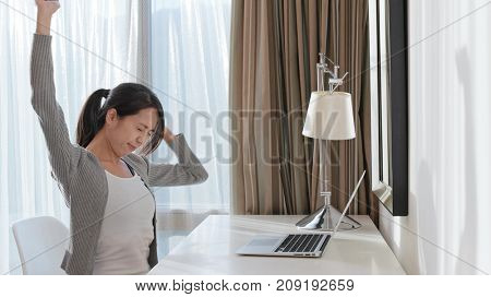 Woman stretching hand after using laptop computer at home
