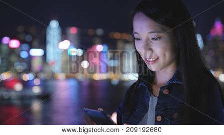 Woman use of mobile phone in Hong Kong Victoria harbor
