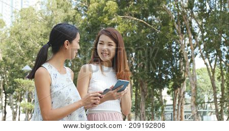 Girls watching video on cellphone together at outdoor