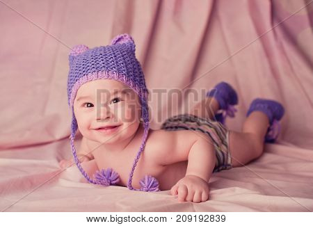Beautiful smiling cute baby portrait lie on a stomach and looking at camera