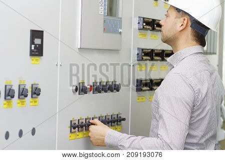Engineer of tech equipment controls. Worker in white helmet on control panel. Monitoring of technology process