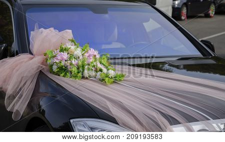 black car with flower ornaments and tulle for the bride and groom during the wedding