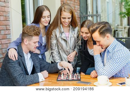 A group of young people in a cafe at a table playing chess. Concept of rest.