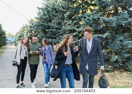Young couple walking with friends. The guy holds the girl's hand. In the background, friends in the background of trees.