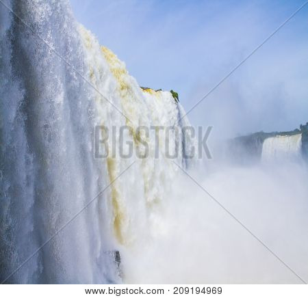 The roaring Iguazu Falls. Border of Brazil, Argentina and Paraguay. Concept of active and extreme tourism