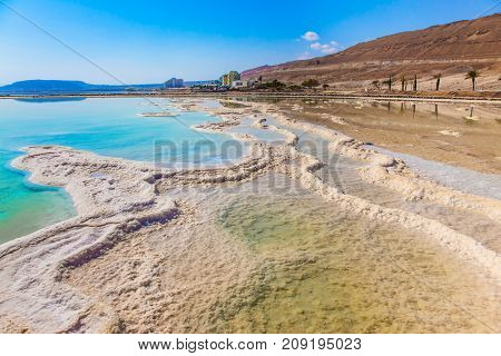 The evaporated salt on the shallow coast of the Dead Sea. Therapeutic Dead Sea, Israel. The concept of medical and ecological tourism