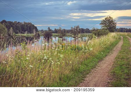 Beautiful summer landscape. Rural road at a beautiful pond.