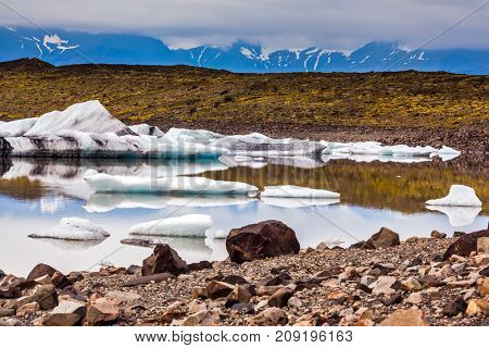 Summer in Iceland.  The lake with splinters of ice floes formed by thawed snow of glacier Vatnajokull.  The concept of northern tourism