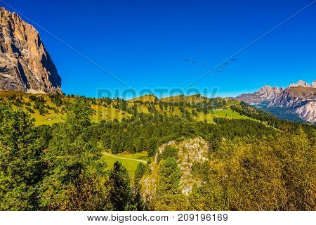 Travel to South Tiro, the Dolomites. The concept of extreme and ecological tourism. Windy autumn day. Grassy plateau on the Sella Pass