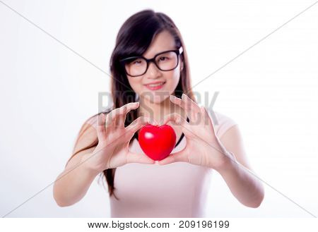 Young asian woman show heart hand sign on white background.