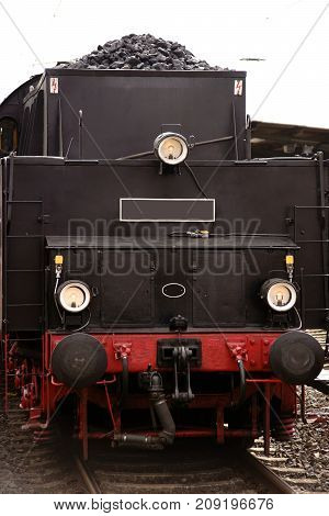 The front view of an old steam locomotive with coal for heating the steam boiler.