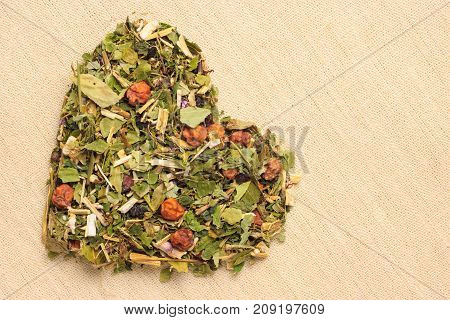 Dried herb leaves heart shaped on burlap jute surface. Herbaceous dry aromatic plant. Healing herbs herbal medicine concept.