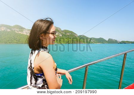 Cute young woman with eyeglasses smiling happily on the boat while cruising the natural of the sea island and under sunlight summer at Mu Ko Ang Thong National Park Surat Thani Thailand