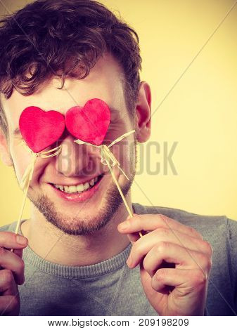 Love romance concept. Man blinded by love. Young male holding hearts on sticks before his eyes.