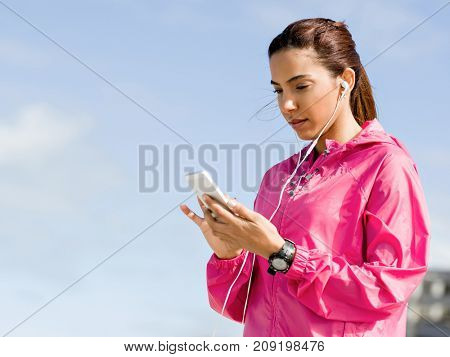 Sporty woman with earphones on the sea coast
