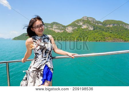 Asian young woman with eyeglasses smiling happily on the boat while cruising the beautiful natural of the blue sea and sky in summer at Mu Ko Ang Thong National Park Surat Thani Thailand