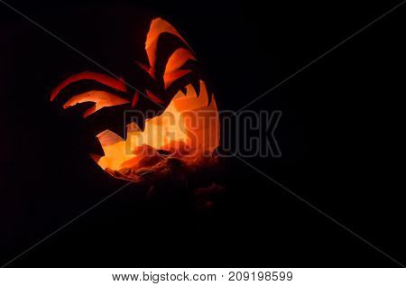 A spooky Halloween pumpkin lit by candles against a black background