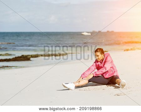 Young woman at the beach doing exercises