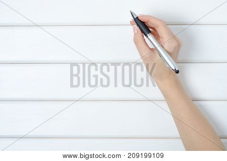 Female hand holding a pen on a white wooden background