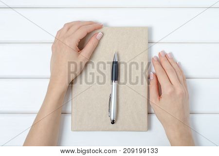 Female hand notepad pen on a white wooden background