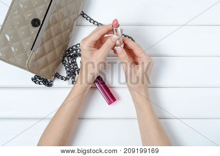 Female hand holding a handbag with lipstick on a white wooden background