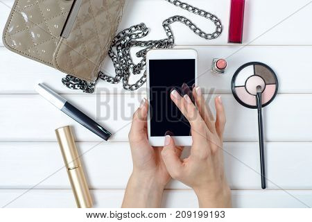 Female hand holding a handbag cosmetic mobile phone smartphone on a white wooden background