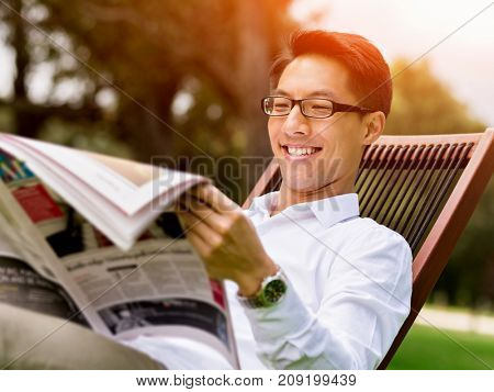 Business man reading a newspaper in park