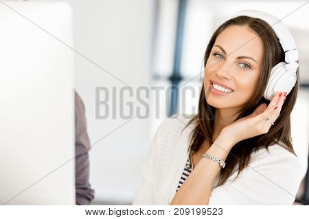 Young woman in the office with headphones