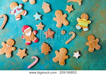 Ginger men with colored glaze on a turquoise background .. Gingerbread. Christmas cookies. Ginger man in a colored sweater. Gingerbread Santa