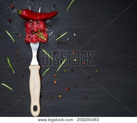 two pieces of beef and red chili pepper strung on a kitchen plug on a black background empty space on the right