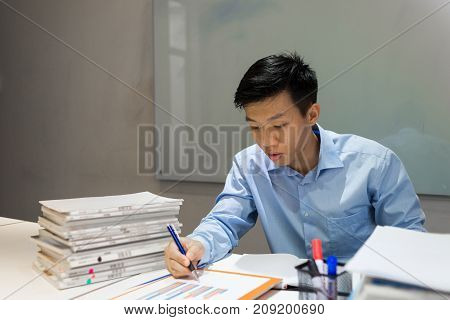Young office employee reading sales report and writing notes