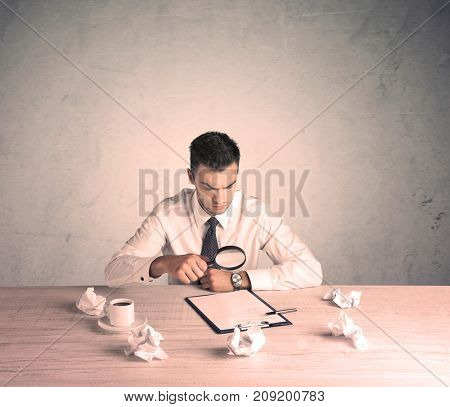 A young office worker sitting at desk working with keyboard, papers, highliter in front of empty clear background wall concept
