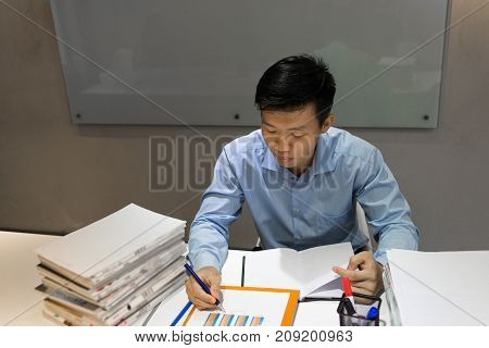 Young man writing notes into the sales report