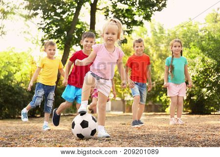 Cute children playing with ball in park