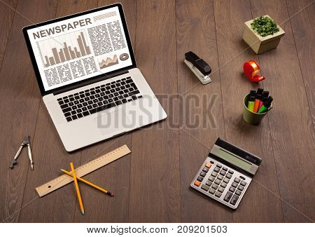 Business laptop with stock market report on wooden desk and accessories