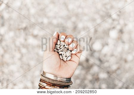 close up of woman hand with manicure on pebble beach background