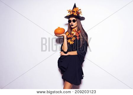 The witch girl was going to a party in the Halloween outfit and holding a pumpkin, a black hat, bats in the background