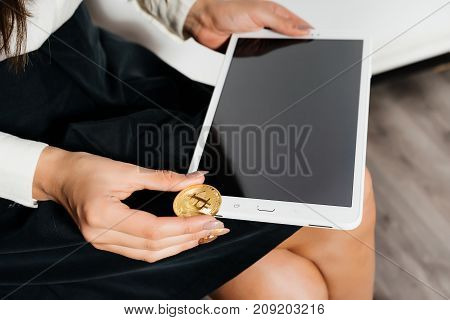 girl with a tablet in her hands. Girl hold a gold coin. Electronic money, Bitcoins, Crypto currency.