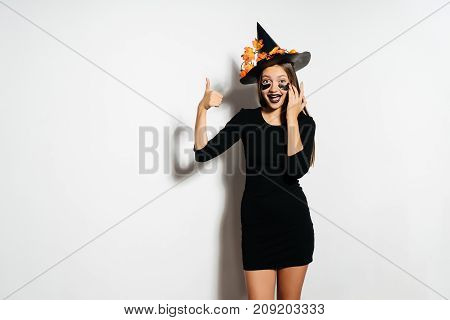 Halloween witch in a terrible suit and hat shows thumbs up and laughs. The girl was going to the Halloween party.