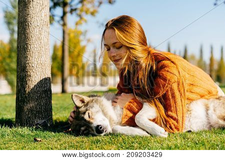 the lovely red-haired girl lies on a green lawn and plays with her dog in the park. An excellent sunny autumn day.