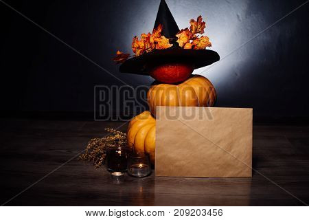 Halloween holidays art design, celebration. Halloween Pumpkins with a witch hat and orange autumn leaves and with the bat