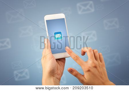 Female fingers touching smartphone with mail icon on it